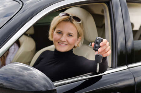 purchased: Proud woman driver holding up her car keys out of the open window of the vehicle to show that she has just purchased a new car