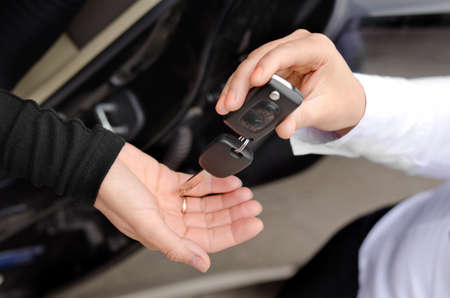 set of keys: Close up view of the hands of a woman handing over a set of car keys to a second woman holding out her hand, conceptual image
