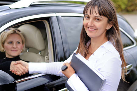 saleslady: Happy attractive saleslady finalising a deal shaking hands with a blond woman who has just purchased a new car from her