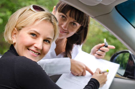 saleslady: Proud successful woman purchasing a car turning to smile at the camera as she and the saleslady prepare to sign the documentation and finalise the deal
