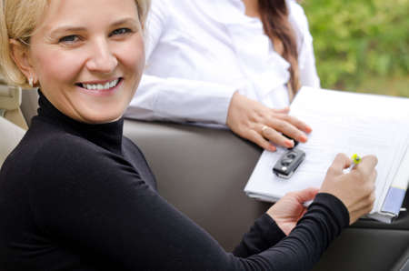 saleslady: Beautiful smiling blond woman signing a contract with a saleslady that will make her the proud owner of a new car Stock Photo