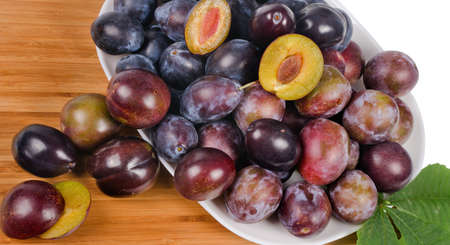 Full frame image of a large group of fresh plums on wooden table photo