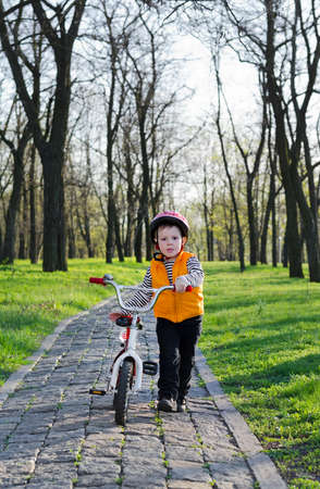 wooded path: Cute little boy in a helmet pushing his bicycle down a cobblestone path in a wooded park