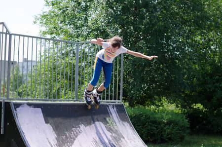 blading: Active energetic young teenage girl roller blading launching herself from the top of a cement ramp in a skate park Stock Photo