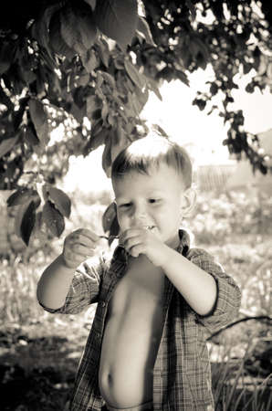 enquiring: Cute little boy studying a wriggling worm with a smile of enjoyment as he holds it up between his hands while playing outdoors in the garden, sepia toned portrait