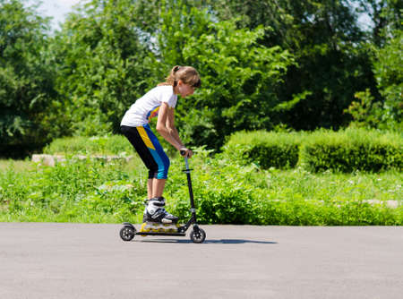 propel: Teenage girl having fun on a scooter as she tries to balance in her roller blades on the footboard and propel herself along the tarmac in a rural park