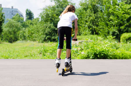 Teenage girl playing on a scooter balancing on the footboard in her roller blades as she travels away from the camera across the asphalt in a rural park photo