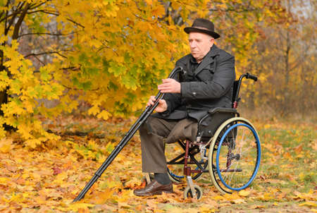amputated: Elderly disabled man with one leg amputated sitting in his wheelchair in the autumn sunshine holding his crutches in a colourful yellow fall park