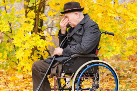 amputated: Despondent despairing senior amputee sitting in his wheelchair outdoors in a colourful yellow autumn park with his head in his hands holding crutches in his hand