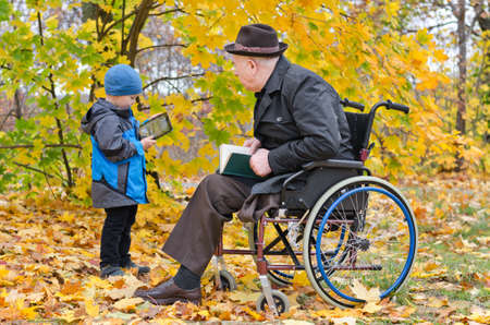 Young boy in the park with his disabled grandfather sitting in a wheelchair showing him something on the screen of his tablet computer