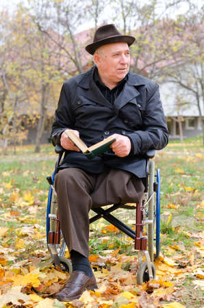 Handicapped elderly gentleman in a wheelchair sitting outdoors enjoying the autumn sunshine with his book