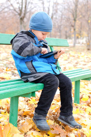 Little boy reading a tablet computer as he sits alone on a wooden bench in the park in autumn amusing himself ,with copyspace photo