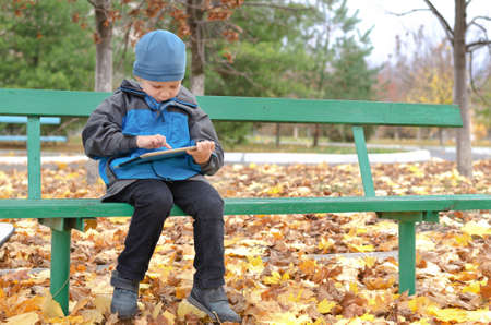 Cute little boy warmly dressed against the cold autumn weather sitting on a park bench surfing on his tablet computer photo