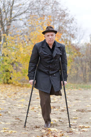 Disabled senior man on crutches determined to continue to enjoy a healthy active lifestyle enjoying a walk in an autumn park in his coat and hat