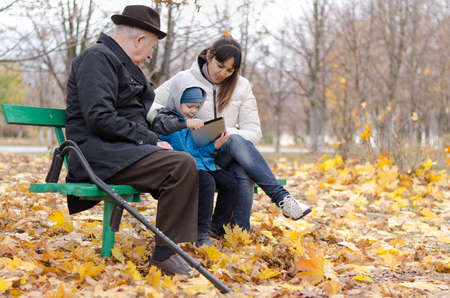 Family enjoying a day in the park with the disabled grandfather on crutches and an attractive middle-aged mother watching a cute young boy play on his tablet computer as the three sit on a bench photo