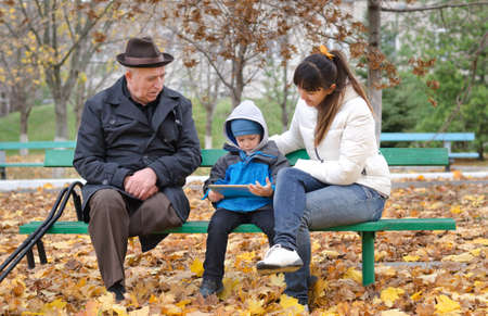 Young boy with his mother and handicapped elderly grandfather playing on a tablet computer as they sit on a bench in the park on a cold autumn day photo