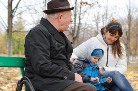 Three generations of a family at the park with an elderly grandfather sitting on a wooden bench with his daughter and grandson photo