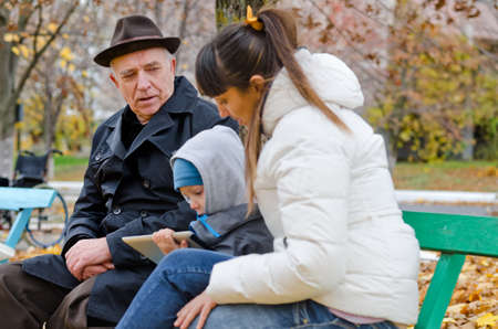 Family outing to the park with an elderly grandfather , his daughter and grandson sitting on a park bench warmly dressed against the autumn chill with the little boy playing on a tablet-pc photo