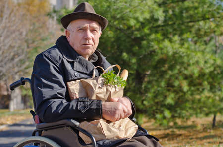 Senior handicapped man doing his grocery shopping sitting in the road in his wheelchair clutching a large bag of food and looking at the camera