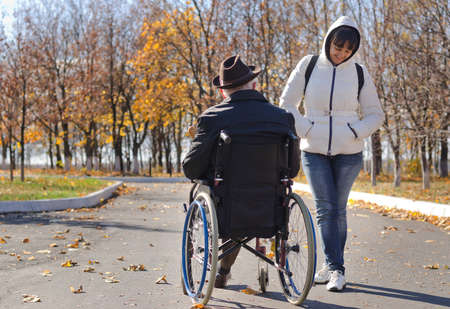 hooded top: Attractive middle-aged woman in a hooded top standing talking to a disabled man in a wheelchair