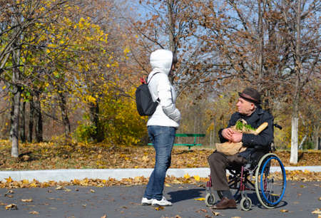 Handicapped senior man in a wheelchair stopping in the street to chat to a woman as he does his grocery shopping photo