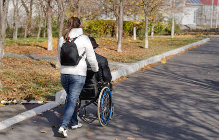 Female carer taking a disabled man in a wheelchair for a walk along the street as they walk away from the camera Stock Photo