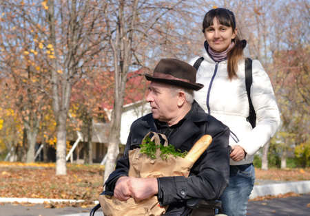 Woman taking an elderly disabled man confined to a wheelchair out shopping for groceries as she pushes his wheelchair along the street in the sunshine