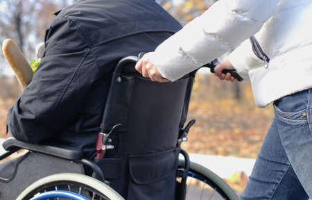 paraplegic: Close up view of the hands of a woman pushing a disabled man in a wheelchair along a rural street in the sunshine