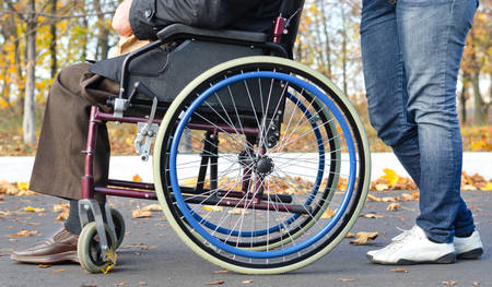 Low angle close up view of a disabled man in a wheelchair with a carer being pushed along a rural tarred street Stock Photo