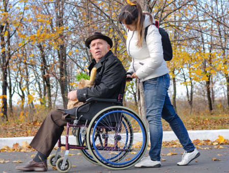 personas ayudando: Mujer que empuja a un hombre de edad avanzada con discapacidad en silla de ruedas a lo largo de una calle rural, ya que volver de hacer la compra juntos Foto de archivo