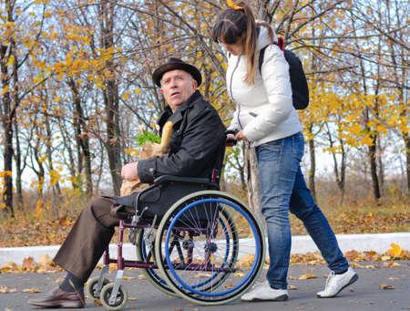 Vrouw duwen een bejaarde gehandicapte man in een rolstoel langs een landelijke straat als ze terugkomen van het doen van de boodschappen bij elkaar Stockfoto