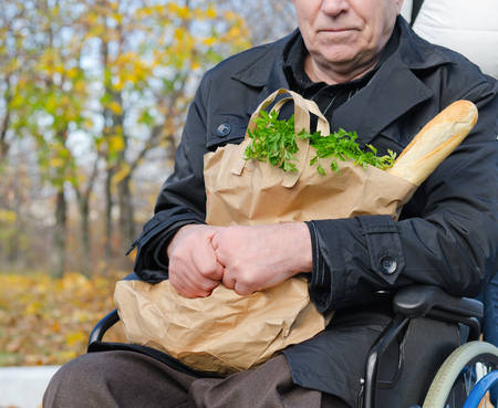 Senior handicapped man doing his grocery shopping sitting in the road in his wheelchair clutching a large bag of food and looking at the camera Stock Photo - 23387907