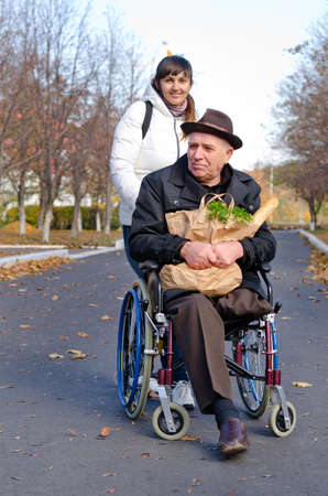Smiling senior man sitting in a wheelchair with a bag of groceries on his lap being pushed along the street by a daughter or carer photo