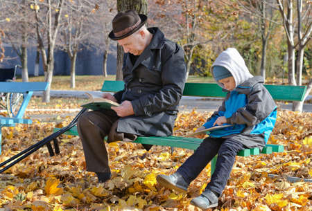 Young boy reading with his disabled grandfather as they sit side by side on a bench in the park on a chilly autumn day enjoying the fresh air and nature photo