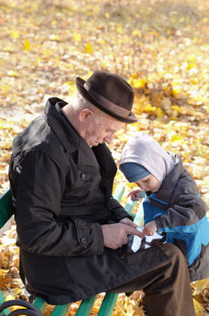 Grandfather and grandson sharing a tablet-pc surfing the internet together as they enjoy a day out in the fresh air at the park on a cold autumn day photo