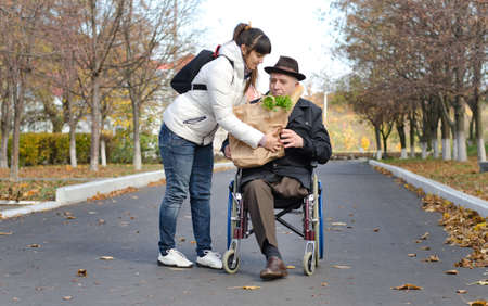 Senior man confined to a wheelchair by a leg amputation being helped with groceries by a woman carer in the street as they return from doing his shopping