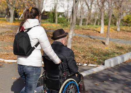 Woman pushing an elderly man in a wheelchair along the street as she takes him out to enjoy the fresh air and autumn sunshine