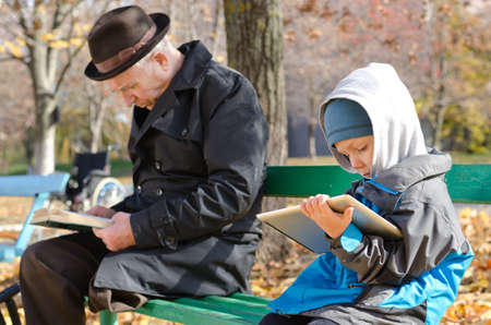 Cute young boy reading an e-book on a tablet computer as he sits alongside his elderly grandfather on a wooden park bench enjoying the autumn sunshine and tranquillity photo