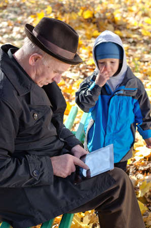 Grandfather using a tablet watched by his cute young grandson wrapped up against the cold autumn weather as they enjoy a day out together sitting on a bench in the park photo