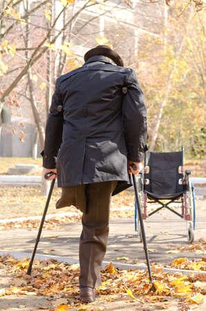 Uitzicht vanaf achter van een gehandicapt one-legged man lopen op krukken in het najaar een park als hij aan het hoofd van zijn rolstoel die is geparkeerd in de straat