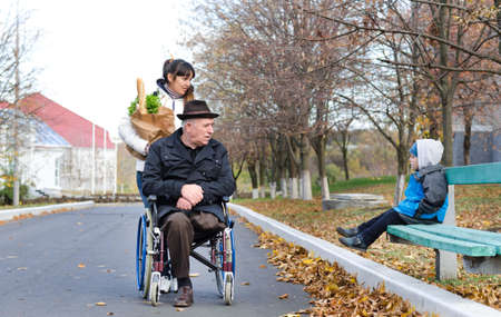 Disabled senior man in a wheelchair and his female carer chatting to a little boy sitting on a park bench as they pause in the street while out doing grocery shopping photo