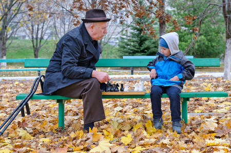 Grandfather playing chess with his little boy sitting back on a park bench