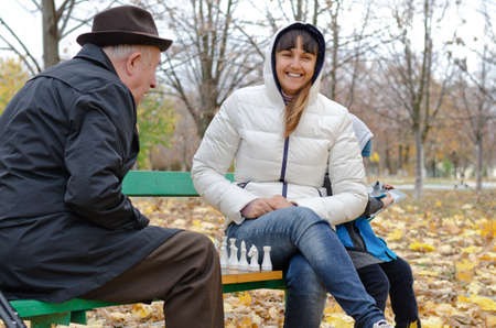 Attractive smiling woman sitting on a park bench playing chess with an elderly man while her young son amuses himself on a tablet computer behind her photo