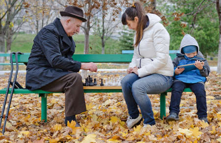 play the old park: Cute young boy sitting on a park bench holding a tablet computer while his mother and grandfather play chess alongside him Stock Photo