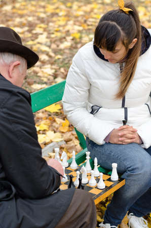 Senior man planning his next chess move staring he plays a game with his daughter as they sit together on a wooden park bench photo