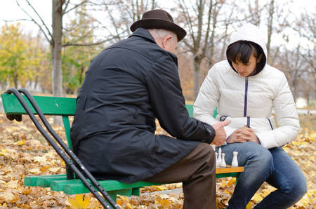 Senior man spending quality time playing chess his granddaughter in an Autumn day, in the park photo