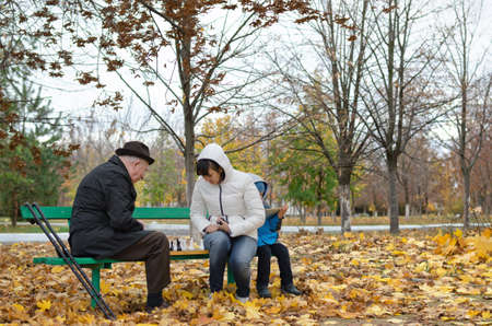 Disabled elderly man with crutches and an younger woman playing chess sitting together on a wooden park bench wrapped up warmly against cold autumn weather photo
