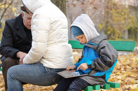 Cute little boy surfing the internet on his tablet computer sitting behind his mother on a wooden bench in the park wrapped up warmly against the autumn chill photo