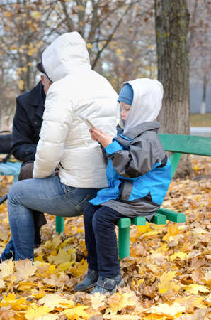 Cute little boy wrapped up against the autumn chill sitting on the end of a wooden bench in the park alongside his mother reading his tablet computer photo