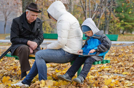 Family spending an autumn day in the park with the elderly grandfather and mother sitting on a bench playing chess while the little boy sits quietly at the end playing on a tablet-pc photo